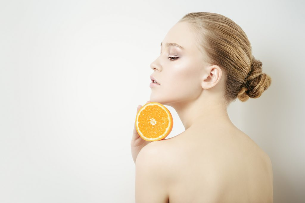 Beauty, natural cosmetics concept. Beautiful young woman with healthy shiny skin holding an orange. White background.