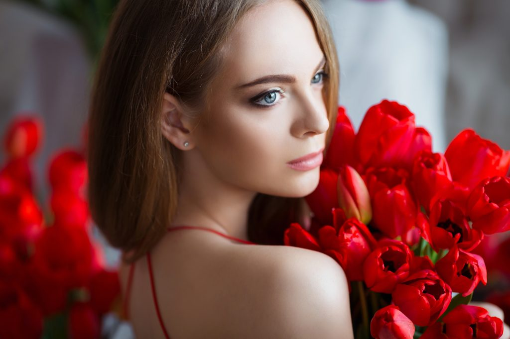 Portrait of young beautiful woman in red dress with tulips in luxury interior