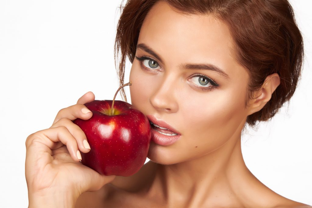 Young woman holding big red apple healthy eating