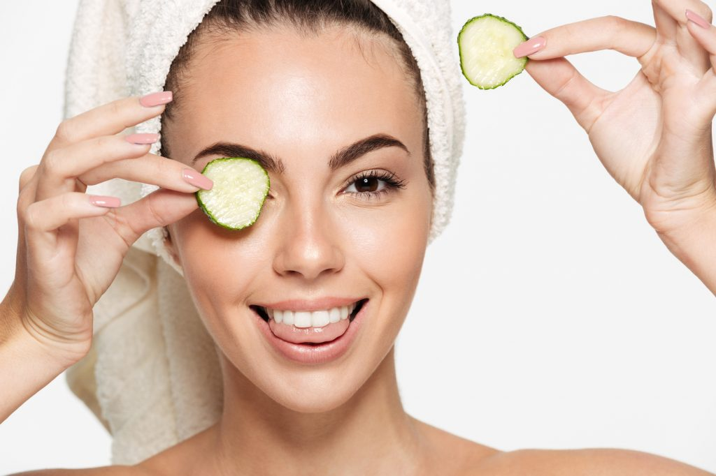 Close up beauty portrait of a smiling beautiful half naked woman with a towel wrapped around her face holding cucumber slices at her face and looking at camera isolated over white background