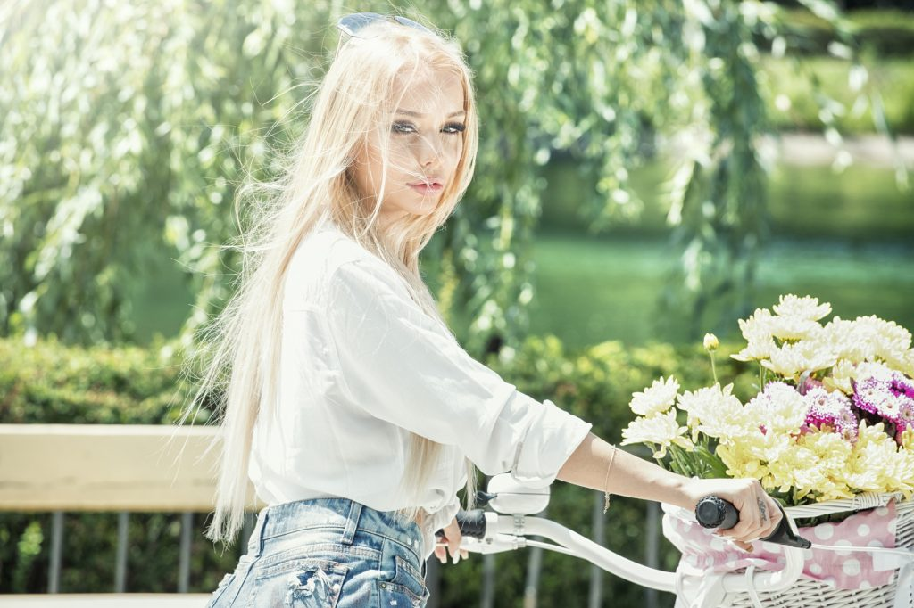Beautiful caucasian blonde girl riding a bicycle with flowers in basket in park. Sunny summer day.