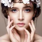 Beautiful woman portrait in tender colors. Young lady posing in studio with flowers on head. Pure skin, nice make up.